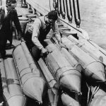 US customs officials examine steel torpedoes on the schooner 'Rosie'. The torpedoes are filled with whisky and  designed to be towed underwater. (Photo by Topical Press Agency/Getty Images)