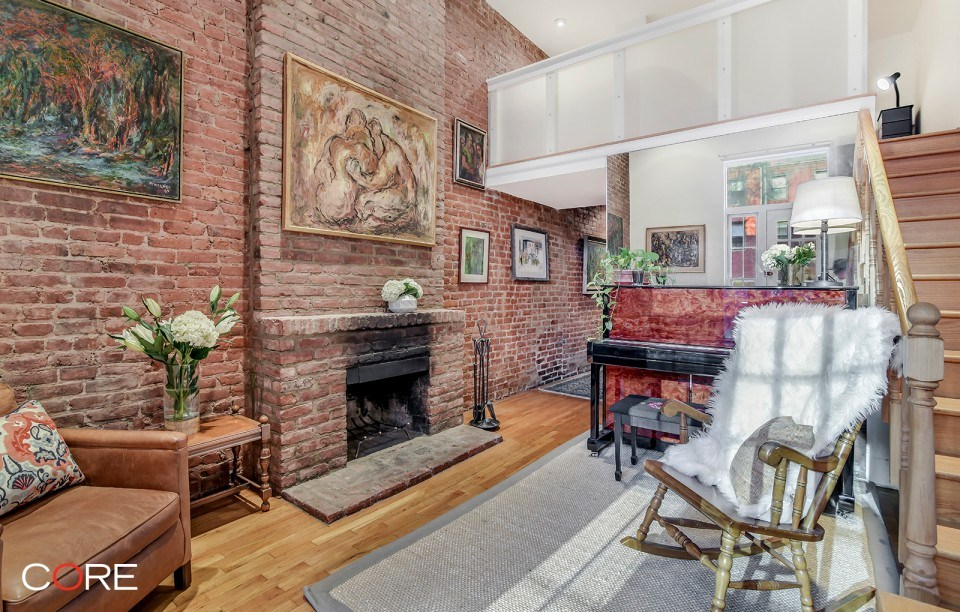 This $845K Chelsea studio's sleep loft, brick walls and terrace are dreamy