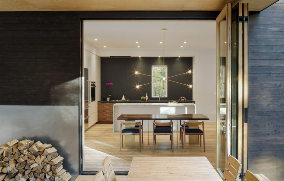 The Architect Designed Both Table And Brass Chandelier Inside Dining Area Here Accordion Glass Doors Blur Line Between Interior