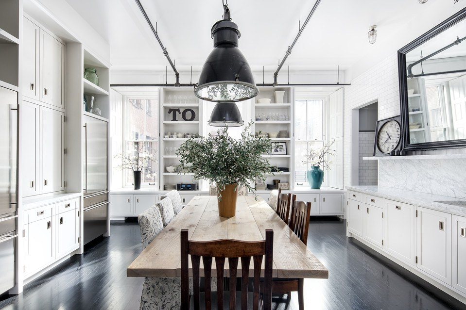 Breathtaking white industrial farmhouse style kitchen with white cabinets, black floors, and huge harvest table. #industrialfarmhouse #modernfarmhouse #farmhousekitchen
