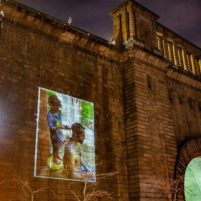 New exhibit projects photos of pandemic parenting moments onto the Manhattan Bridge